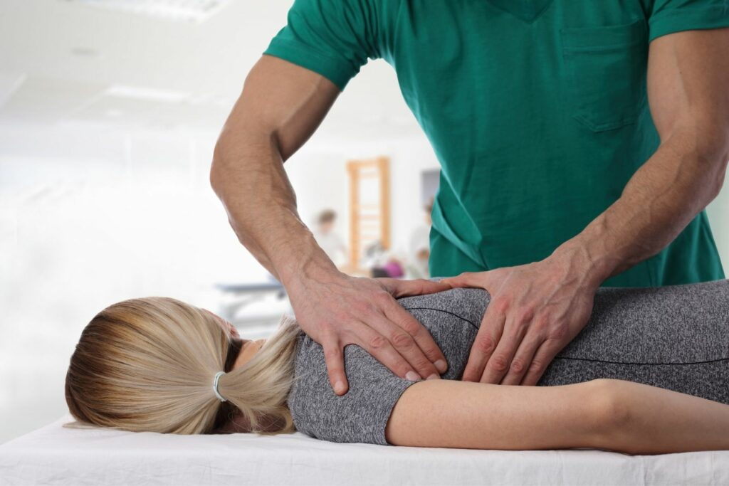 chiropractor in green shirt giving an adjustment to a blond female