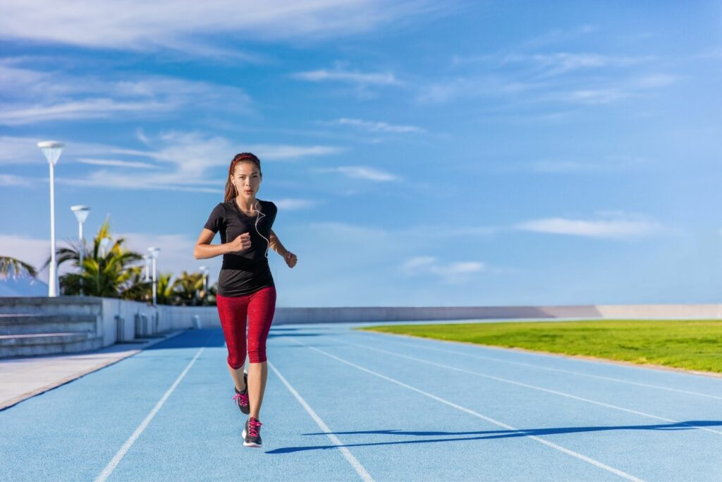 woman running against a blue sky on a track circle with red pants to showcase all athletes are accepted at elite chiropractors in maryland